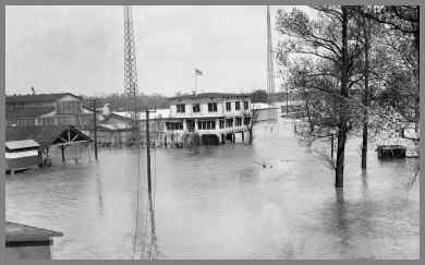 Flooded WUG2 site showing towers and frame building with water all around