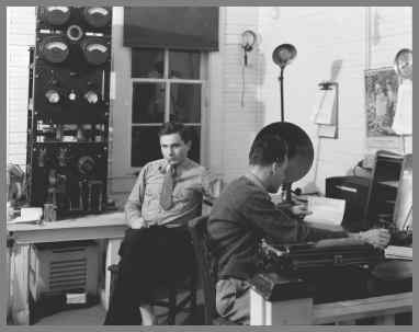 WUG2 radio room with transmitter in background and one operator relaxing with a pipe and another at a desk on the right pounding the key.