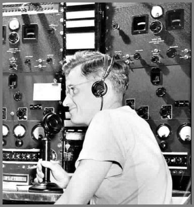 Al Klopp at the WAS mic in the 1950s. Receivers and other gear behind him.
