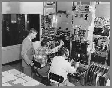 Two operators sitting in front of equipment rack panels at small rack panel mounted desks. Supervisor standing on the left.