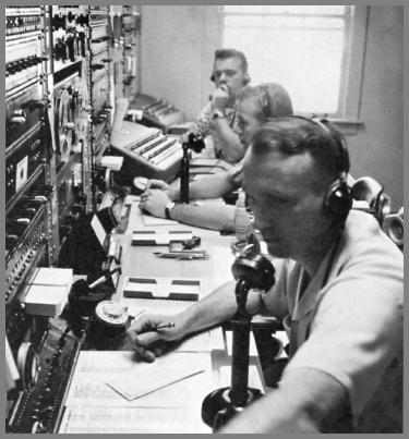 Three operators at a larger 1962 operating console.