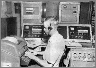 Paul Hise at the TTY with console beside him and transmitters in the background.
